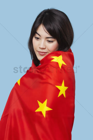 Respect : Patriotic young woman wrapped in chinese flag over blue background