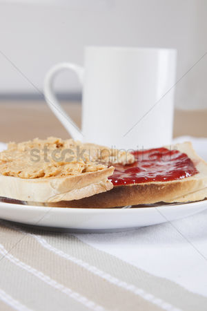 Ready to eat : Peanut butter and jam on slices of bread with cup of coffee