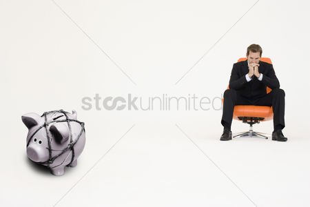 Rope : Pensive businessman on chair and piggybank tied with rope representing financial difficulties