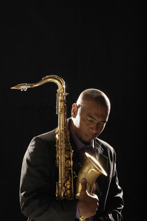 Bald : Pensive man holding saxophone eyes closed