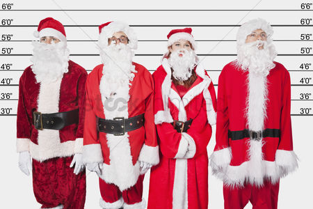 Three quarter length : People in santa costume standing side by side against police lineup