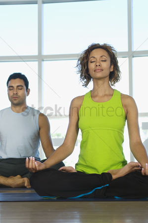 Two people : People meditating during yoga class