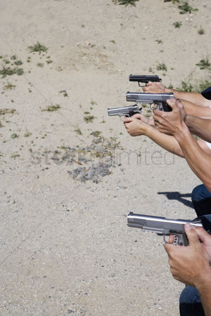 Firing : Peoples aiming guns at firing range close up of hands