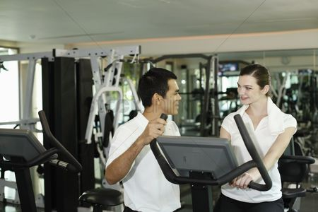 Club : Personal trainer helping woman exercising in gymnasium
