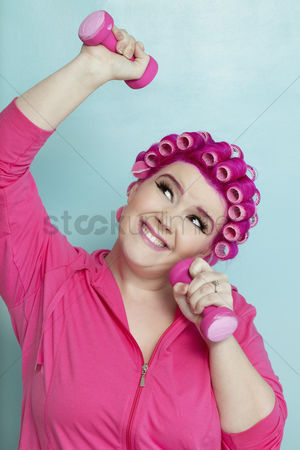 Loss : Playful young woman lifting weights over colored background