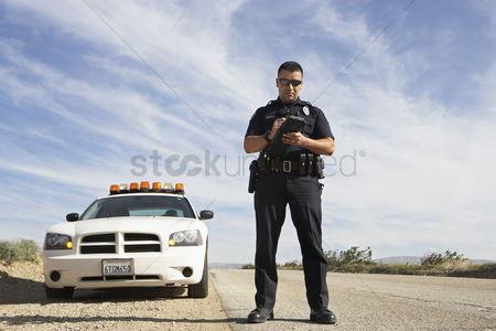 Land : Police officer taking notes in front of police car