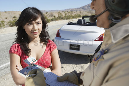 Frowning : Police officer ticketing  young woman driver on desert highway