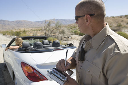 Notepad : Police officer writing a ticket for a convertible driver