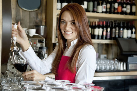Employee : Portrait of a beautiful young waitress removing wine in bar