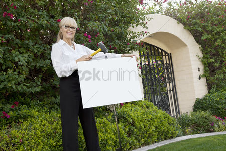 Blank : Portrait of a happy senior female agent hammering sign board in lawn
