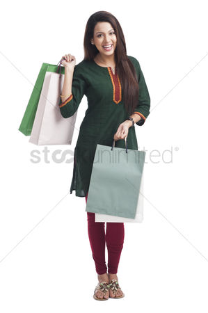 Housewife : Portrait of a happy woman carrying shopping bags