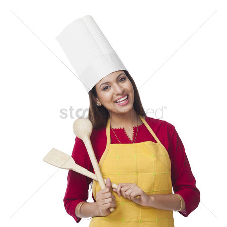 Housewife : Portrait of a happy woman holding a spatula and ladle