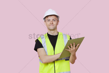 Supervisor : Portrait of a male construction worker with clipboard over pink background