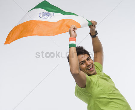 Respect : Portrait of a man holding aloft an indian flag