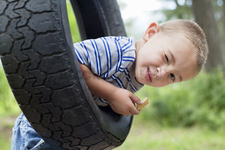 Rope : Portrait of a young boy winking while swinging on tire