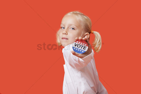 Ponytail : Portrait of a young girl showing vote badge over pink background