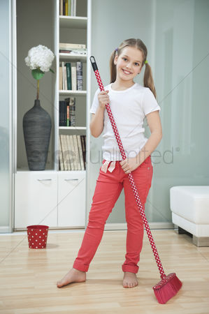 Pre teen : Portrait of a young girl sweeping floor with broom