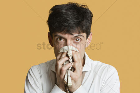 Blowing : Portrait of a young man blowing nose over colored background