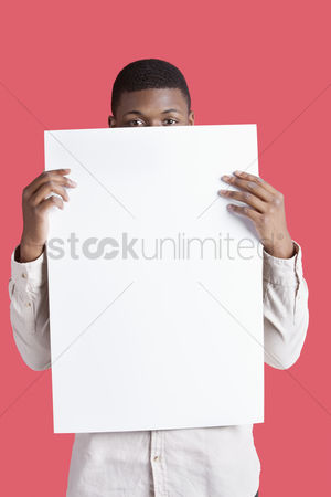 Cardboard cutout : Portrait of a young man holding blank cardboard in front of face over pink background