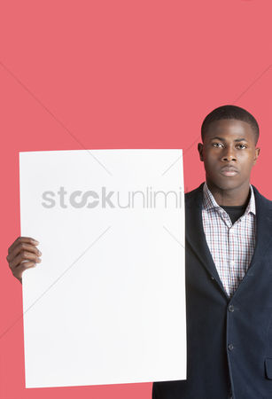 Cardboard cutout : Portrait of a young man holding blank cardboard over pink background