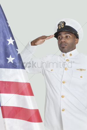 Respect : Portrait of a young us navy officer saluting american flag over gray background