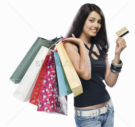 Spending money : Portrait of a young woman holding shopping bags and a credit card