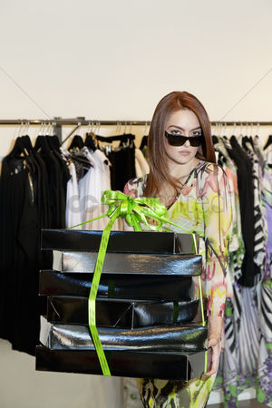Spending money : Portrait of a young woman wearing sunglasses carrying boxes in fashion clothing store