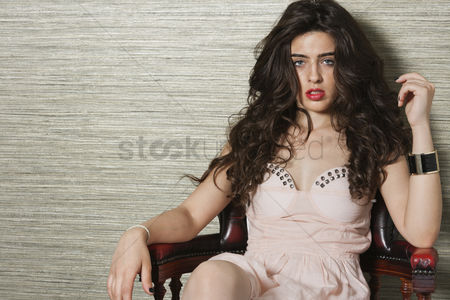 Beautiful : Portrait of an attractive young woman sitting on chair over textured background