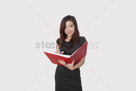 Supervisor : Portrait of beautiful young businesswoman writing notes in folder over white background