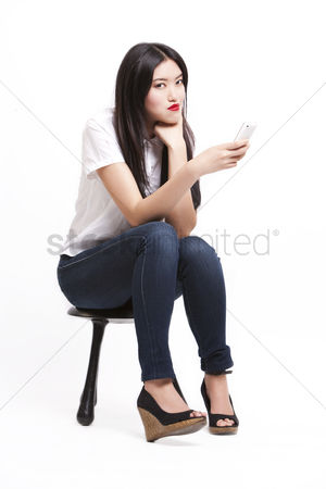 Cell phone : Portrait of beautiful young woman in casuals sitting on stool with mobile phone against white background