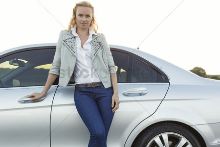 Land : Portrait of beautiful young woman standing by car at countryside