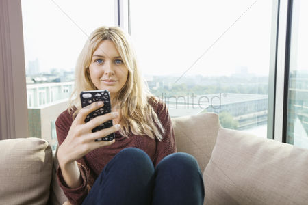 Cell phone : Portrait of beautiful young woman with mobile phone at home