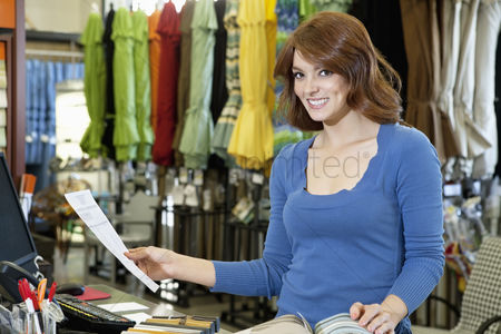 Supermarket : Portrait of beautiful young woman with paper and textile samples standing in store