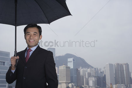 Moody : Portrait of business man with umbrella smiling