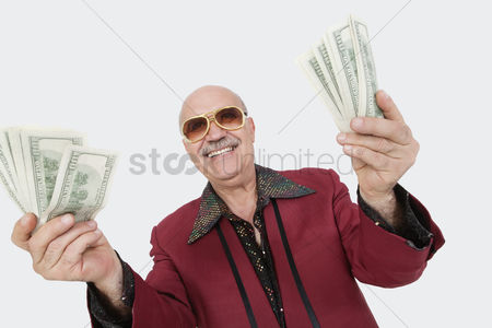 Man suit fashion : Portrait of cheerful senior man showing us banknotes against gray background