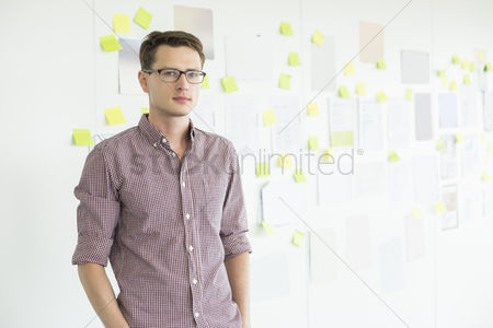 Creativity : Portrait of confident businessman standing against whiteboard in creative office