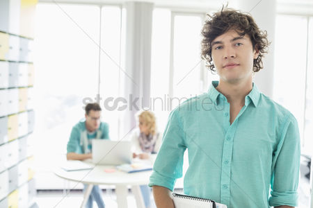 Creativity : Portrait of confident businessman with colleagues working in background at creative office