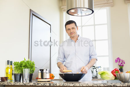 Houseplant : Portrait of confident man preparing food in kitchen