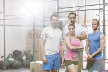 Muscle training : Portrait of confident men and women standing at crossfit gym