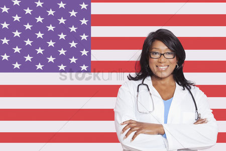 Respect : Portrait of confident mixed race female surgeon over american flag