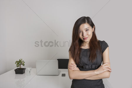 Asian : Portrait of confident young businesswoman standing arms crossed in office