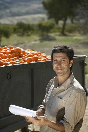 Truck : Portrait of farmer standing by truck with oranges