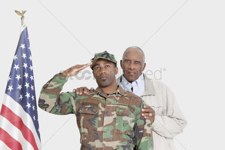 Respect : Portrait of father with us marine corps soldier saluting american flag over gray background
