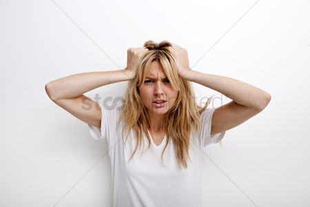 Young woman : Portrait of frustrated woman pulling against white background