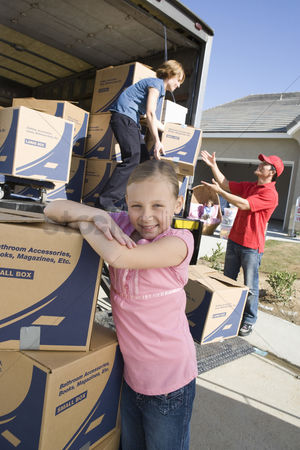 Truck : Portrait of girl  7-9  by truck of cardboard boxes