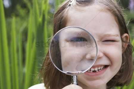Magnifying glass : Portrait of girl  7-9  looking through magnifying glass