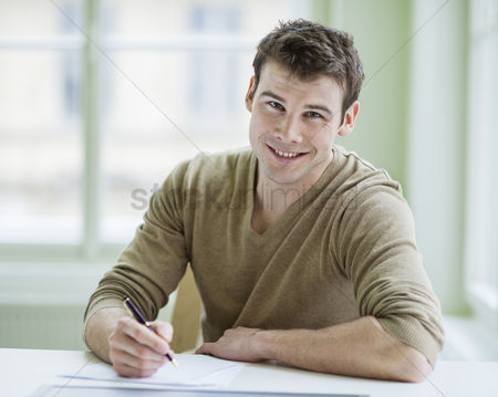 Czech republic : Portrait of handsome businessman writing on document at desk in office