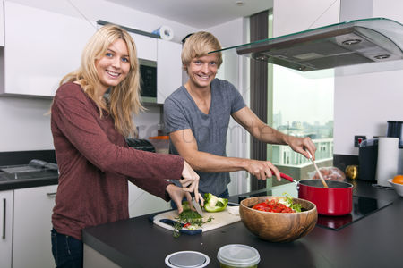 Bowl : Portrait of happy caucasian couple cooking together in kitchen