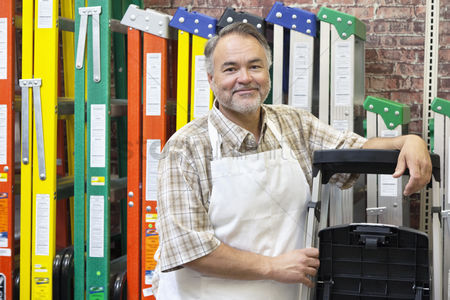 Apron : Portrait of happy mature store clerk standing by multicolored ladders in hardware shop