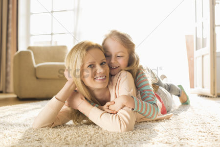 Two people : Portrait of happy mother with daughter lying on floor at home